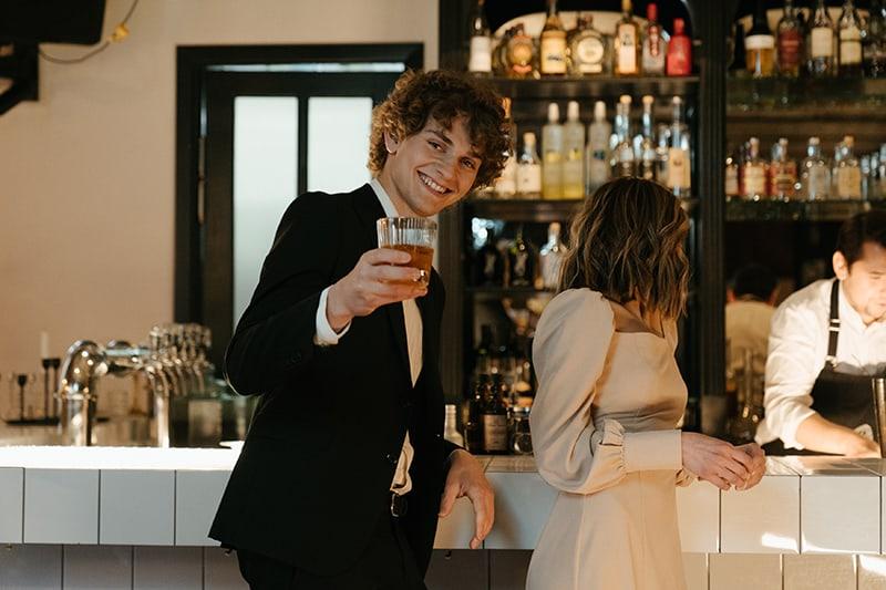 ein lächelnder Mann, der einen Drink hält, während er neben einer Frau steht, die sich an die Theke lehnt