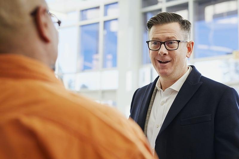 Ein lächelnder Mann spricht mit einem anderen Mann, während er vor dem Gebäude steht