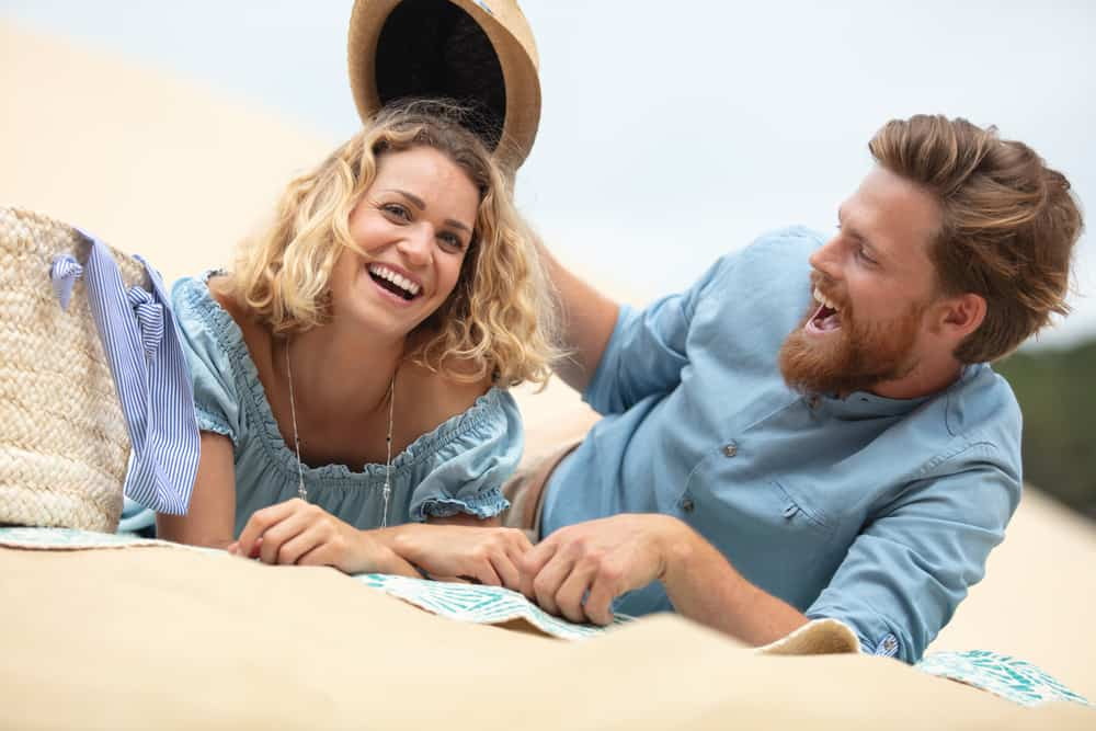 ein lächelndes Liebespaar, das am Strand liegt und Spaß hat