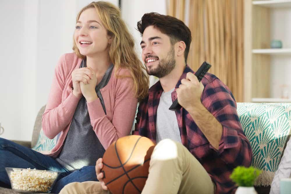 ein lächelndes Liebespaar, das ein Basketballspiel im Fernsehen genau beobachtet