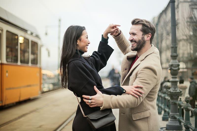 Ein lächelndes Paar tanzt tagsüber auf dem Bürgersteig