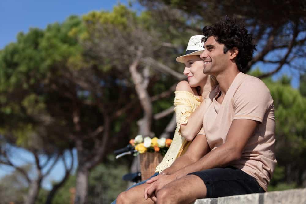 ein liebendes Paar sitzt auf Beton in der Sonne