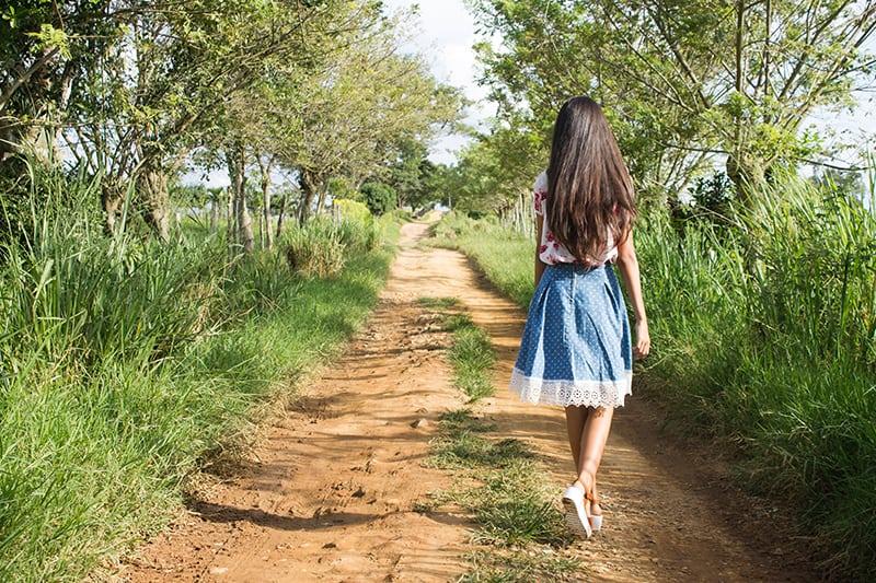 eine Frau, die auf der Straße nahe dem grünen Gras geht