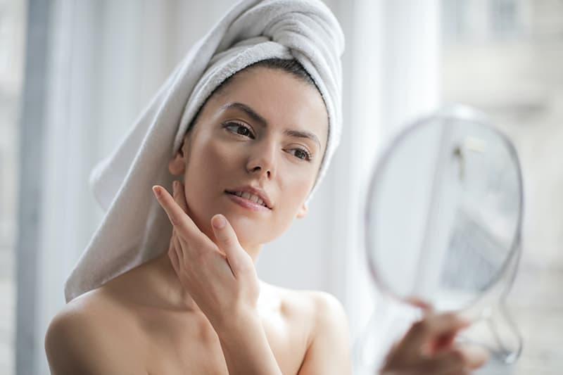 Eine Frau, die Creme auf das Gesicht aufträgt und sich selbst in den Spiegel schaut