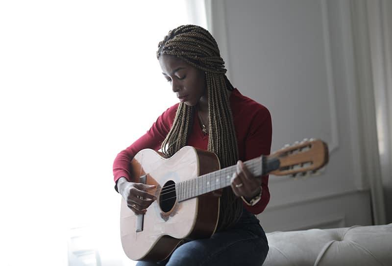 eine Frau, die lernt, Gitarre zu spielen, während sie auf der Couch sitzt