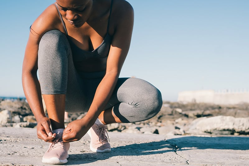 eine Frau, die Schnürsenkel auf der Straße bindet
