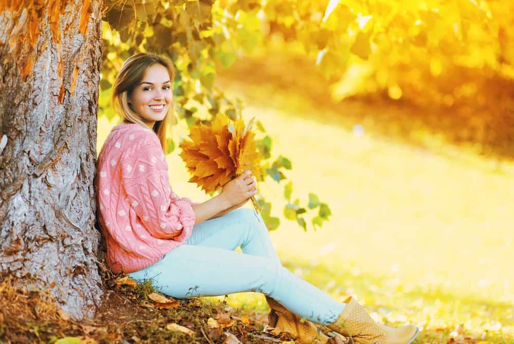 eine Frau, die an einem Baum mit einem Blatt in der Hand sitzt