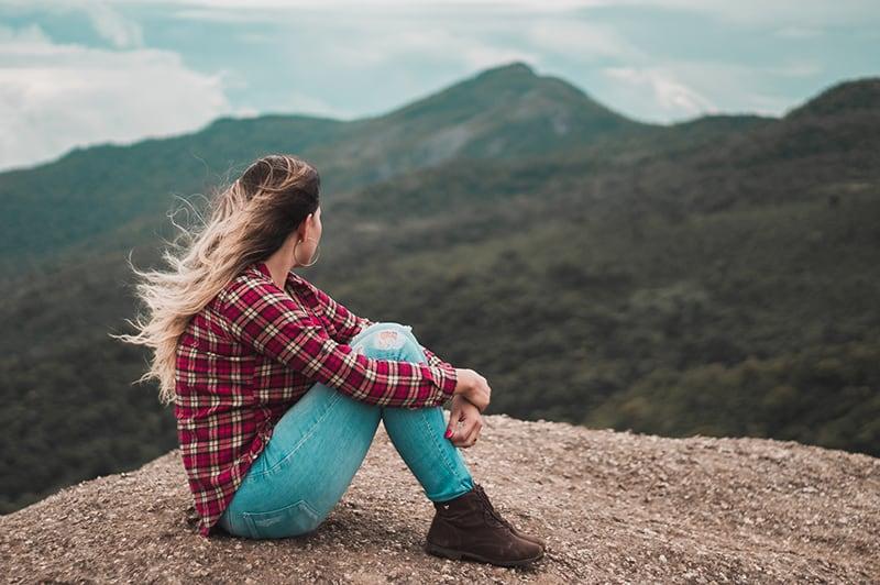eine Frau, die auf dem Boden sitzt, während sie denkt und einen Hügel überblickt