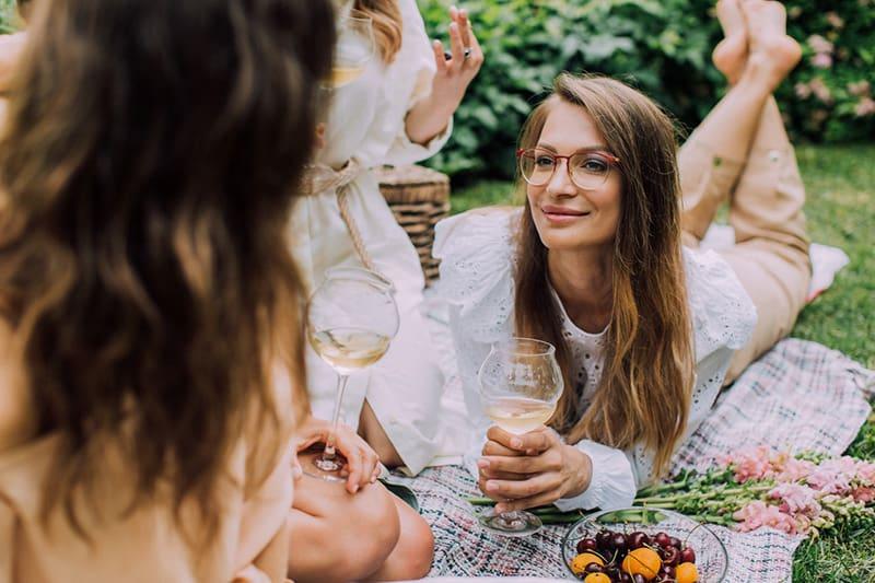 eine Frau, die auf einer Decke liegt und ihre Freundin ansieht, während sie zusammen Wein trinkt