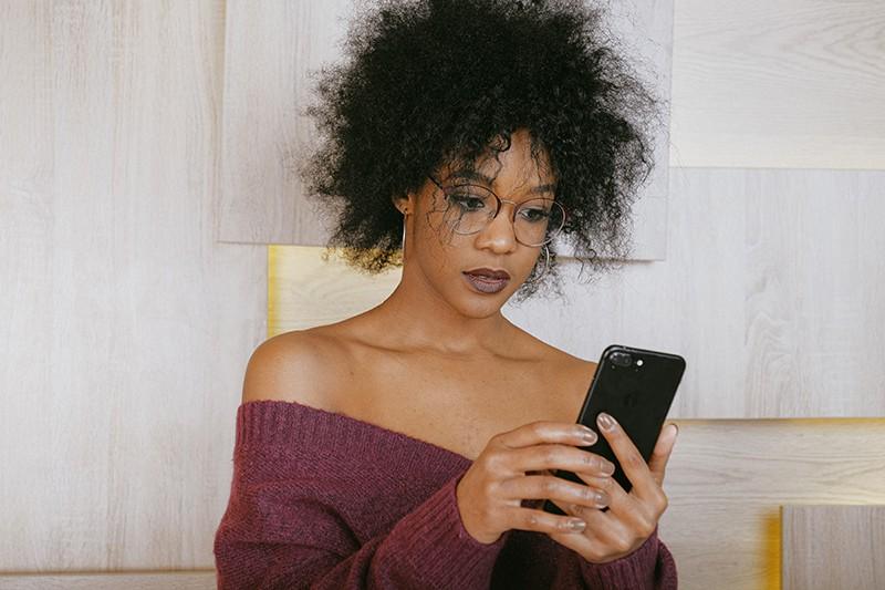 eine Frau, die ihr Smartphone betrachtet, während sie nahe der Holzwand steht