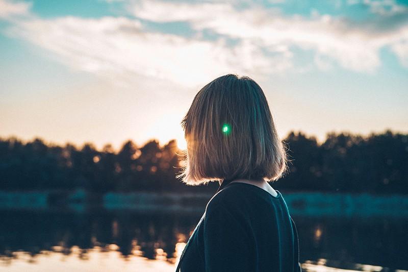 eine Frau, die den Sonnenuntergang beobachtet, während sie in der Nähe des Sees steht