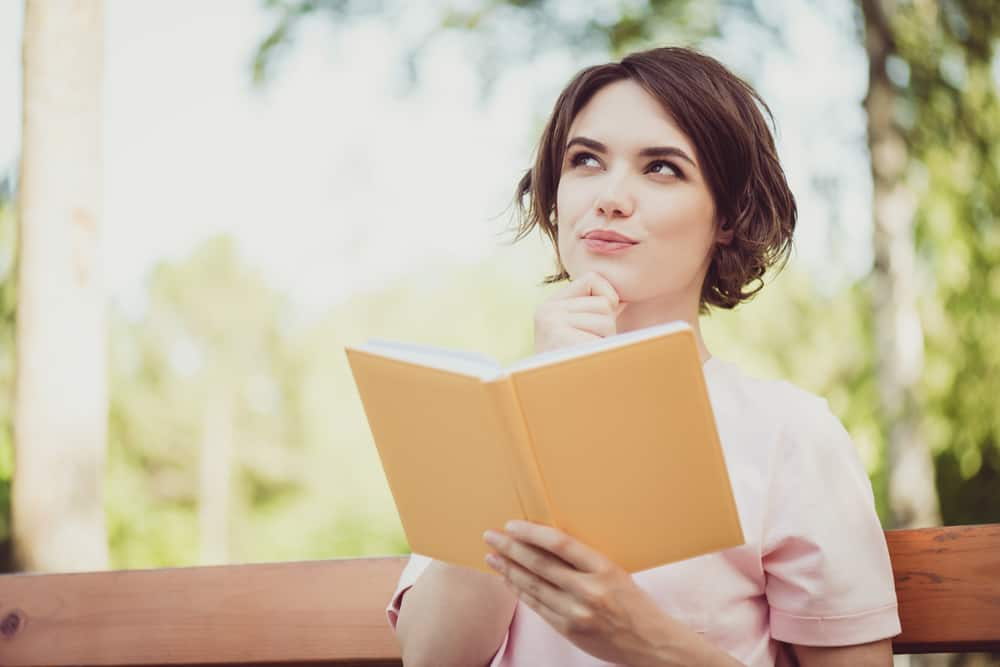 eine Frau, die draußen mit einem Buch in der Hand sitzt und positiv denkt