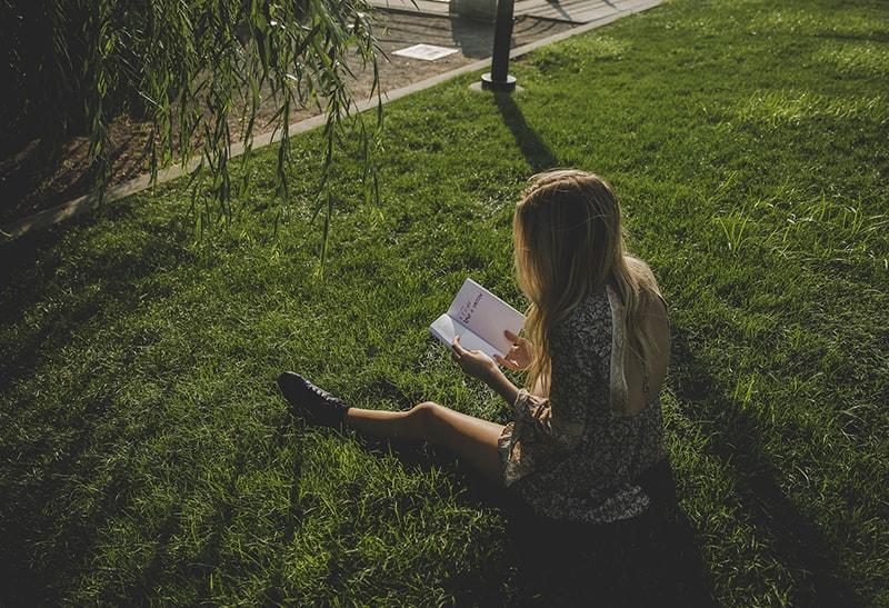 eine Frau, die ein Buch liest, das auf dem Gras sitzt