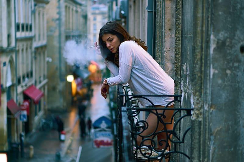 eine Frau, die auf dem Balkon eine Zigarette raucht
