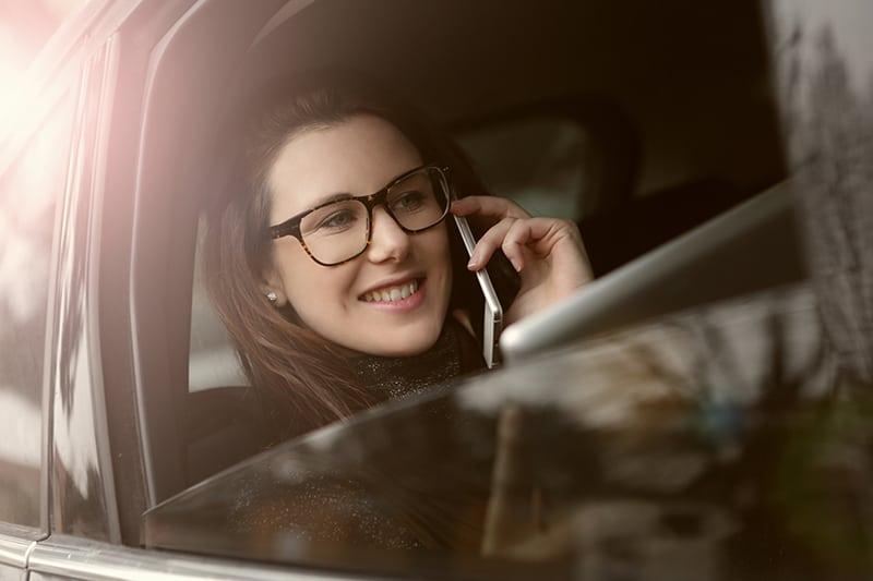 eine Frau, die einen Anruf hat, während sie im Auto sitzt