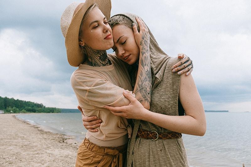 eine Frau, die einen Freund tröstet, während er am Strand steht
