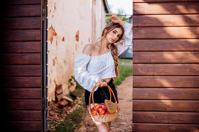 eine Frau, die einen Korb mit Pfirsichen hält, während sie auf dem Tor steht