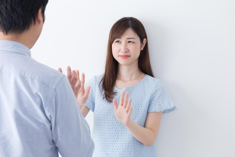 eine Frau, die einen Mann ablehnt, der mit ihren Handflächen vor ihr steht