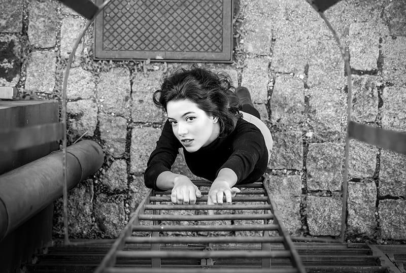eine Frau, die gerade die Feuerleiter erklimmen will und nach oben schaut