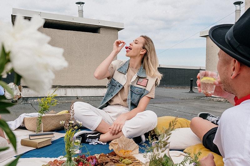 eine Frau, die gerade eine Kirsche essen will, während sie mit einem Freund auf der Decke sitzt