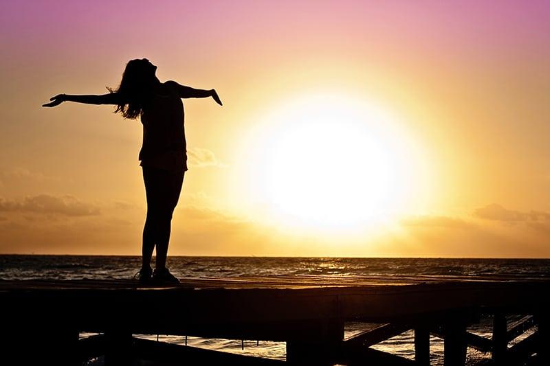eine Frau, die ihre Arme hebt und während eines Sonnenuntergangs in den Himmel schaut