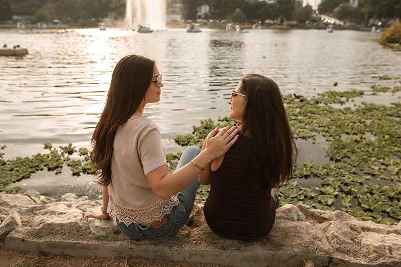 eine Frau, die ihre Freundin tröstet, während sie zusammen in der Nähe des Sees sitzt
