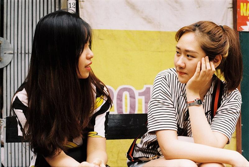 eine Frau, die ihren Freundinnen zuhört, während sie zusammen auf der Bank sitzen