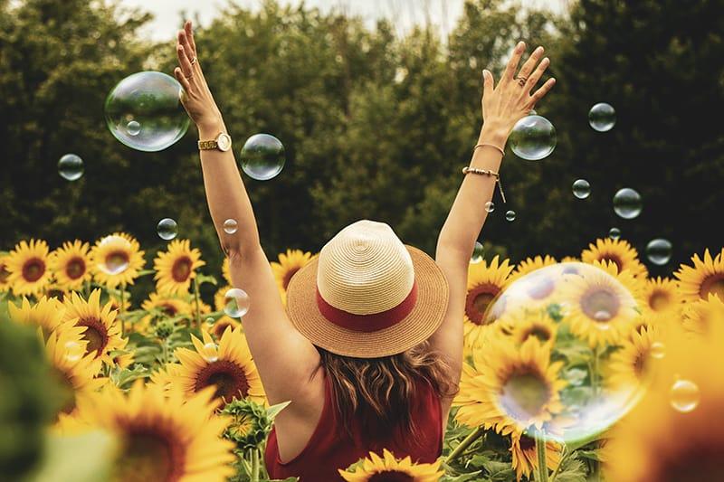 eine Frau, die im Sonnenblumenfeld steht und ihre Hände hebt