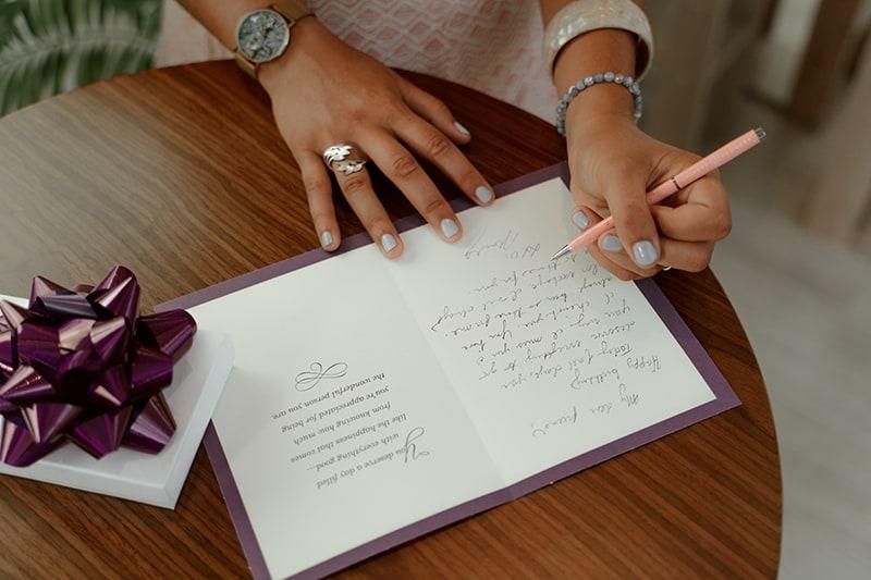 eine Frau, die auf eine Geburtstagskarte mit einem Geschenk in der Nähe schreibt