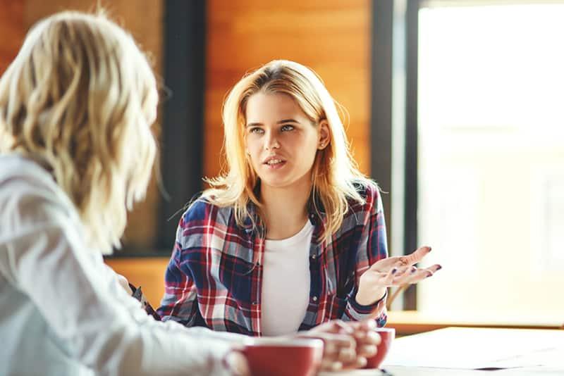 eine Frau, die mit einem Freund spricht und mit der Hand gestikuliert, während sie im Café sitzt