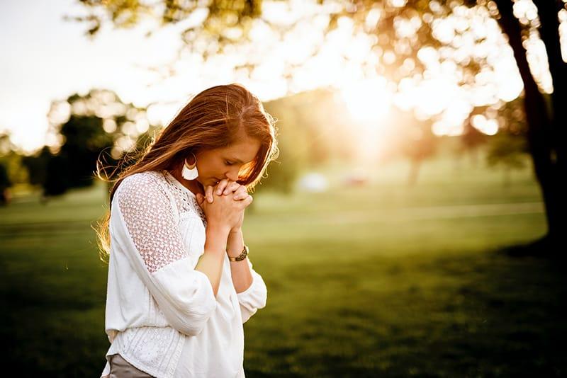 eine Frau, die neben einem Baum im Park betet