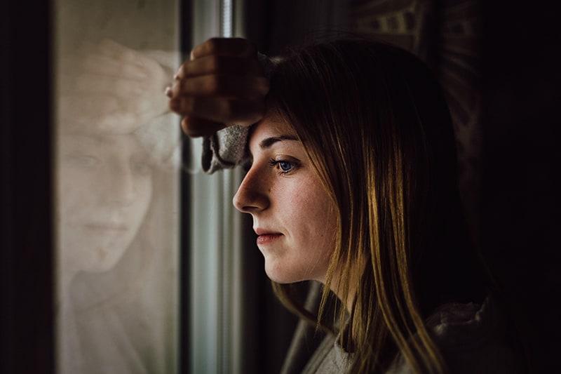 eine Frau, die sich an das Glasfenster lehnte und nachdachte