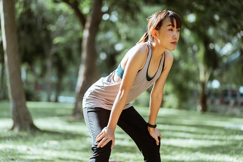 eine Frau, die sich nach einem Training in einem Park ausruht