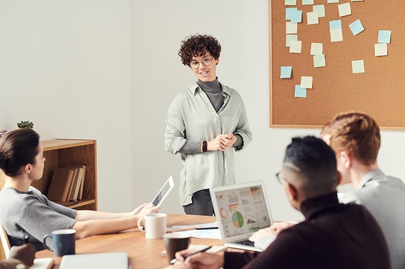 eine Frau, die während eines Treffens vor ihren Kollegen steht