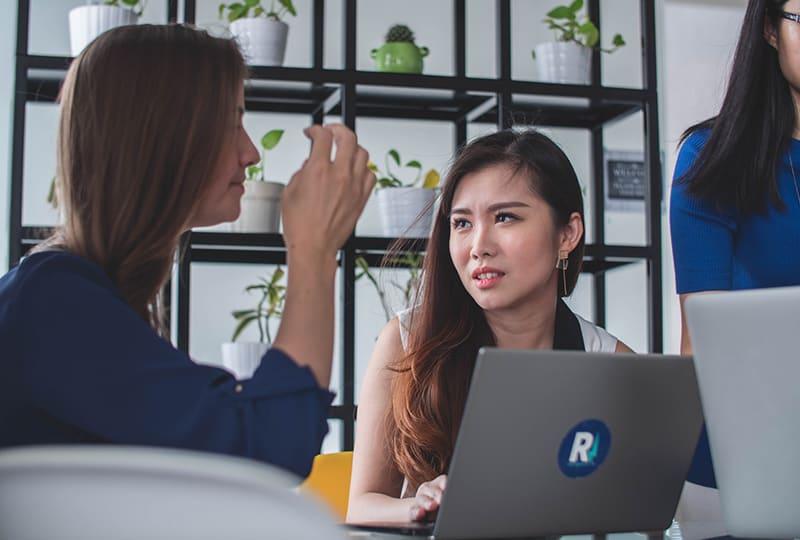 eine Frau, die auf ihre Kollegin schaut, während sie über Arbeit spricht