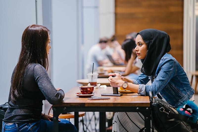 eine Frau in einer Jeansjacke, die ihrer Freundin gesteht, während sie im Café sitzt