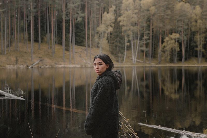 eine Frau, die in der Nähe des Sees im Wald steht