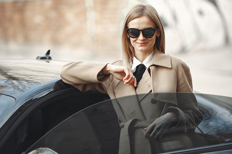 eine Frau in einem beigen Mantel, die sich auf das Auto stützt
