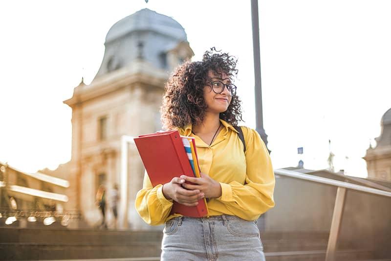 eine Frau in einem gelben Hemd, das Bücher hält, während sie auf der Treppe steht