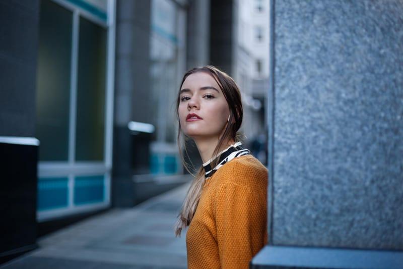 eine Frau in einem orangefarbenen Pullover an der Wand gelehnt