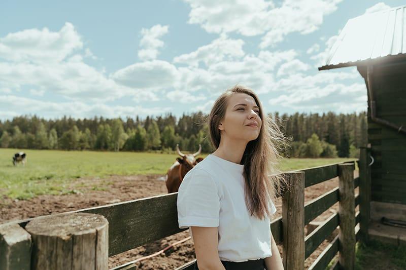 eine Frau in einem weißen T-Shirt, die sich auf den Holzzaun vor dem Stier stützt
