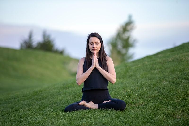 eine Frau, die meditiert, während sie tagsüber im Gras sitzt