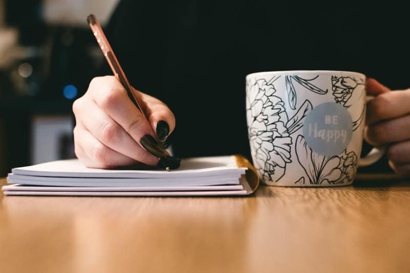 eine Frau mit Kaffee schreibt