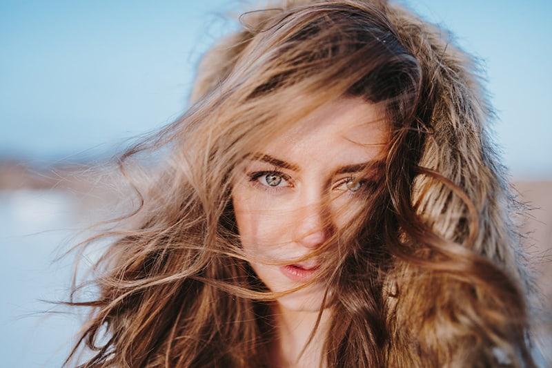 eine Frau mit blonden Haaren, die tagsüber im Wind stehen