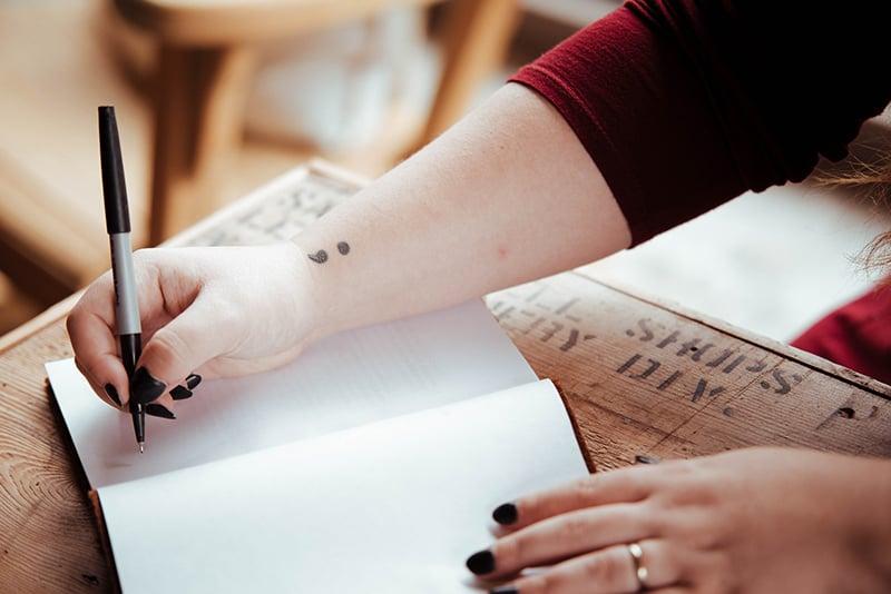 eine Frau, die einen Bleistift in der Hand hält, um in ein Notizbuch zu schreiben