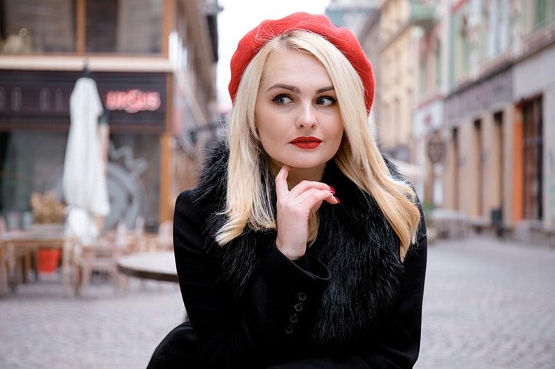 eine Frau mit einem roten Hut, der beiseite schaut und nachdenklich aussieht, während sie auf der Straße steht