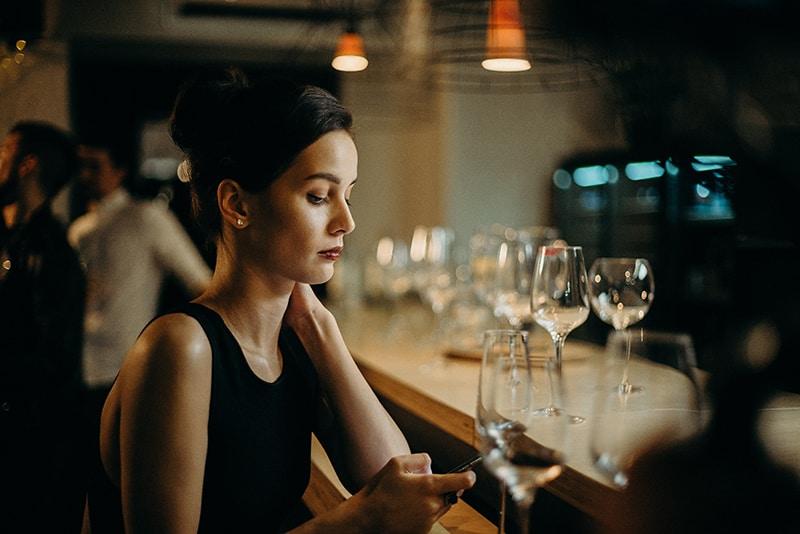 eine Frau, die ihr Smartphone benutzt, während sie alleine an der Theke sitzt