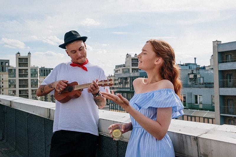 eine Frau singt, während ein Mann die Ukulele auf dem Dach spielt