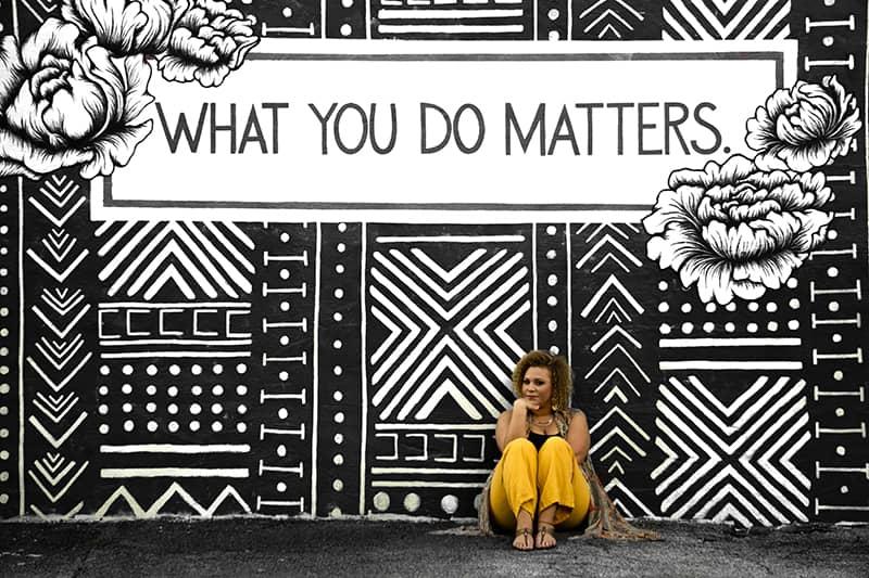 eine Frau, die auf dem Boden nahe der Graffitiwand sitzt
