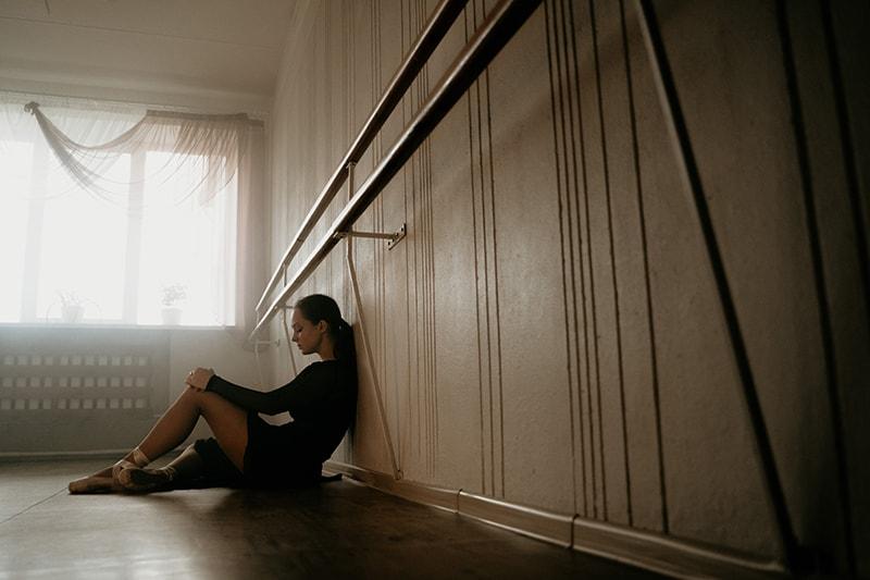 eine Frau, die auf dem Boden sitzt und nachdenklich aussieht